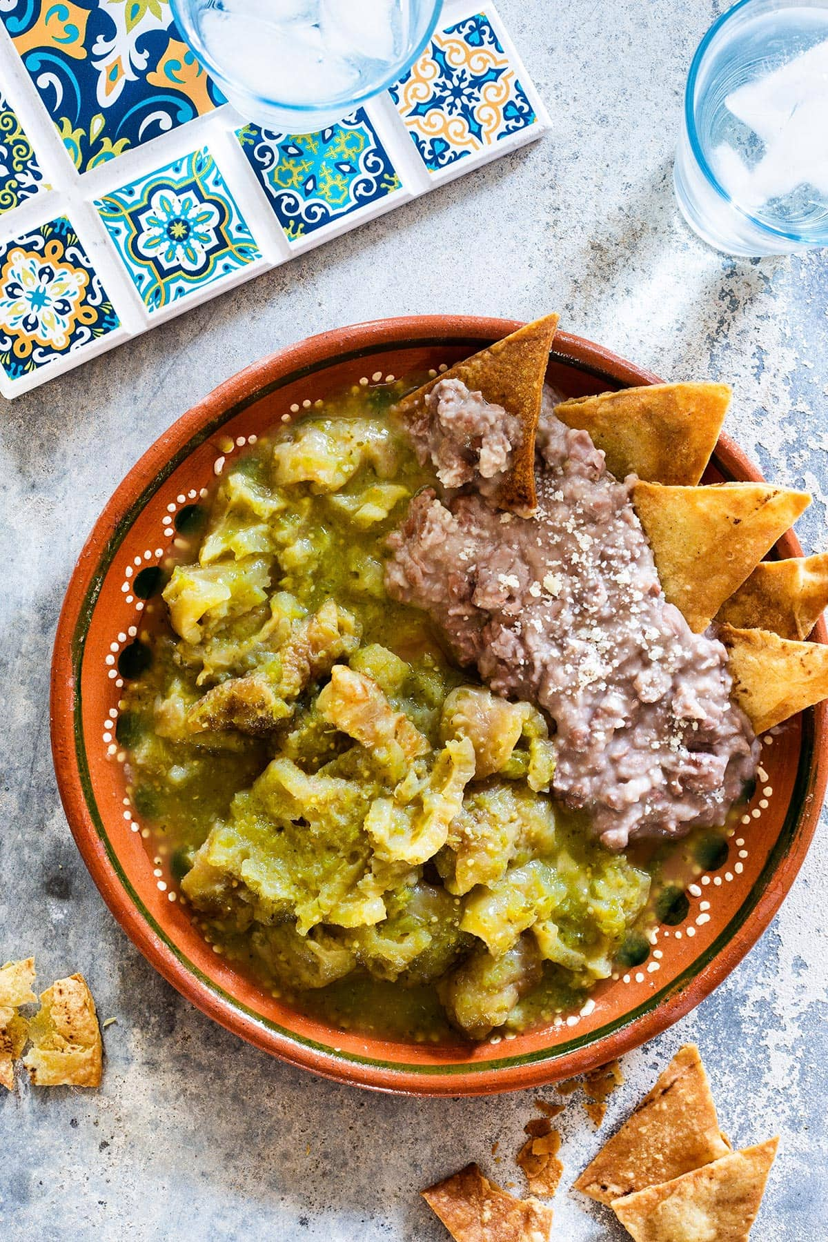 Chicharron en salsa verde served with refried beans and corn chips.