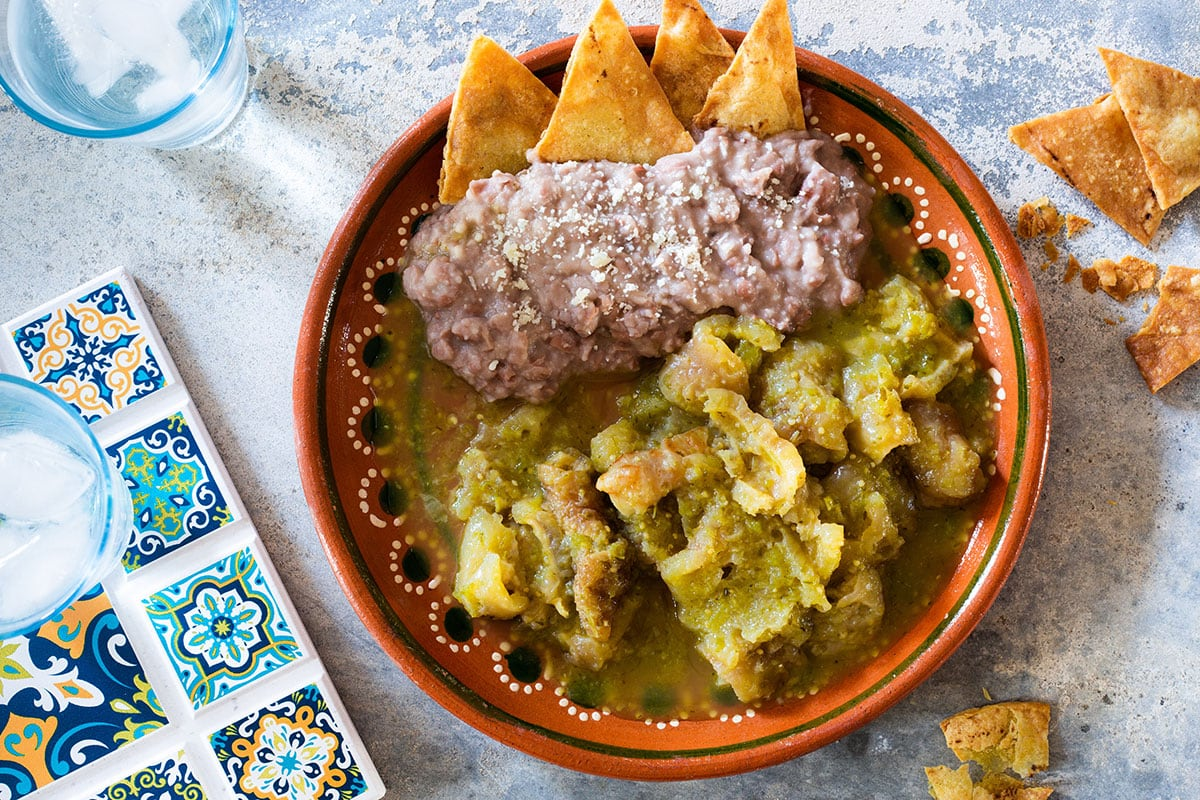 Chicharrones in salsa verde served with refried beans and tortilla chips.