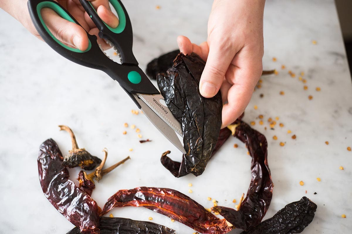 Cutting Mexican chilies with scissors.