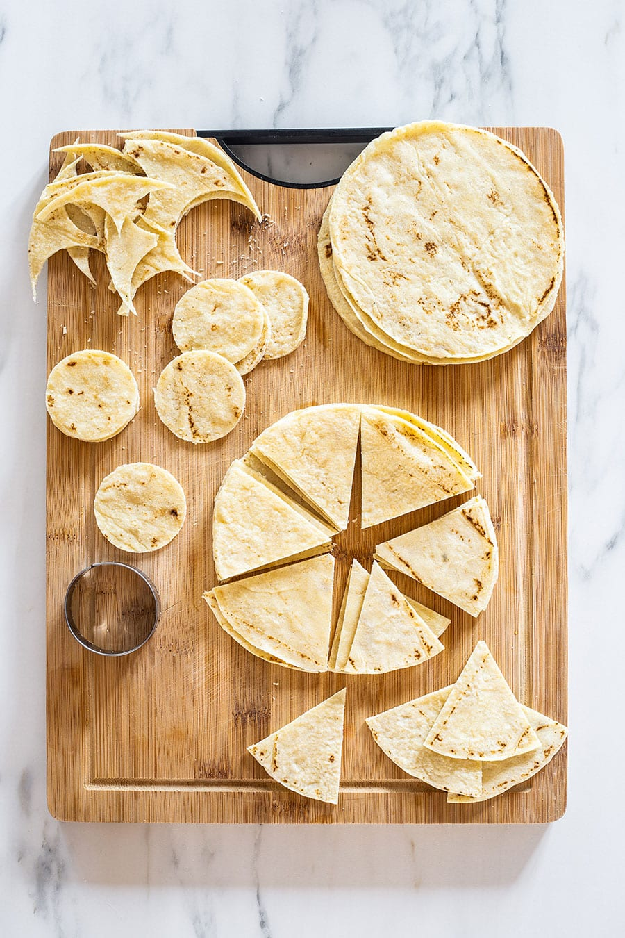 Tortillas cut into various shapes on a cutting board.