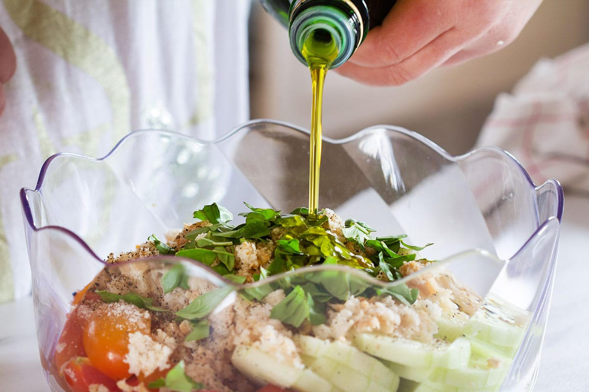 Adding olive oil to panzanella salad.