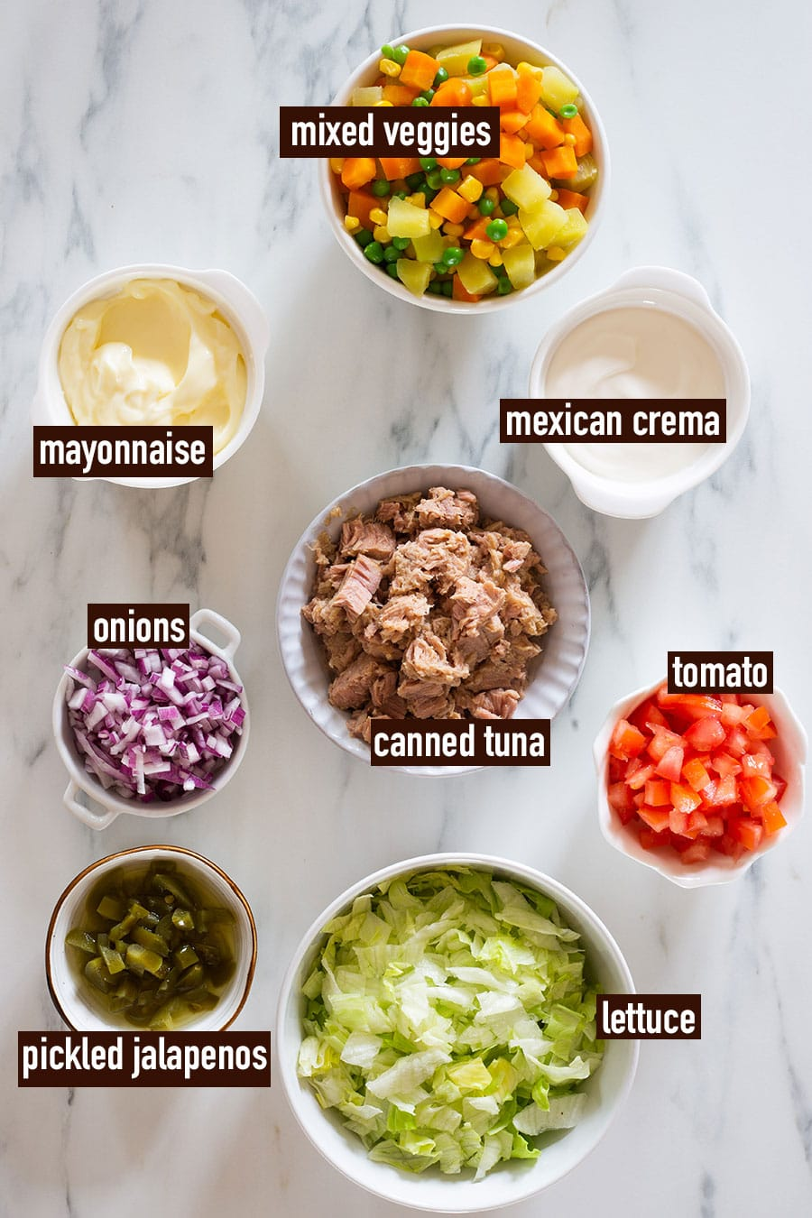 All ingredients ready on bowls and labeled with names placed on a marble surface.