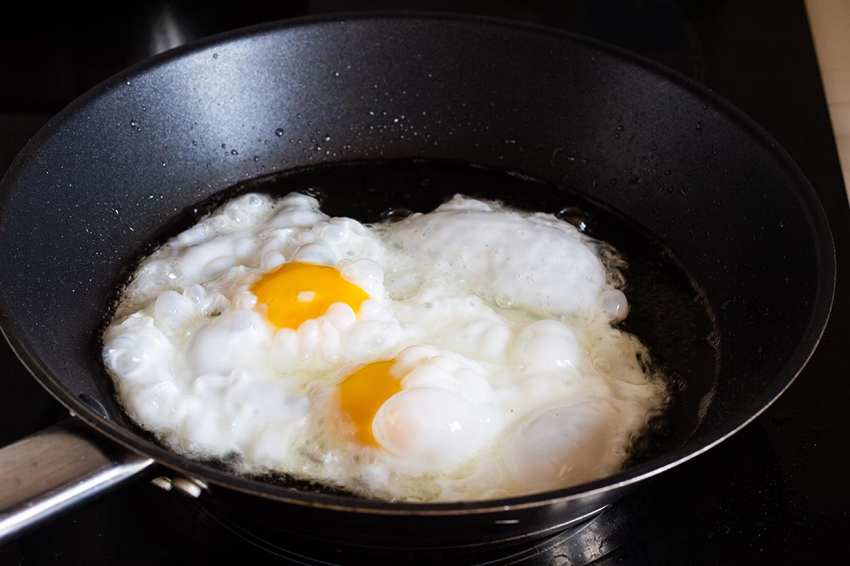 Two eggs frying on a pan.
