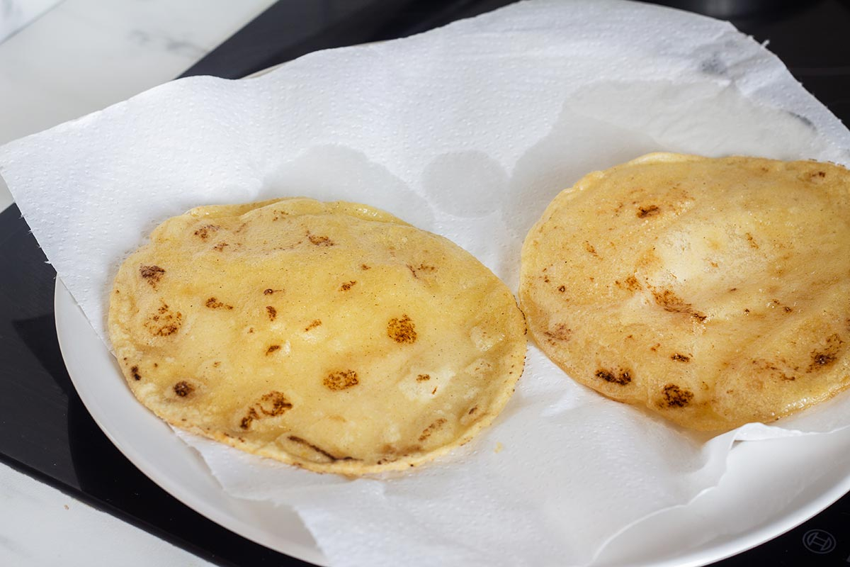 Fried tortillas over kitchen paper towels.