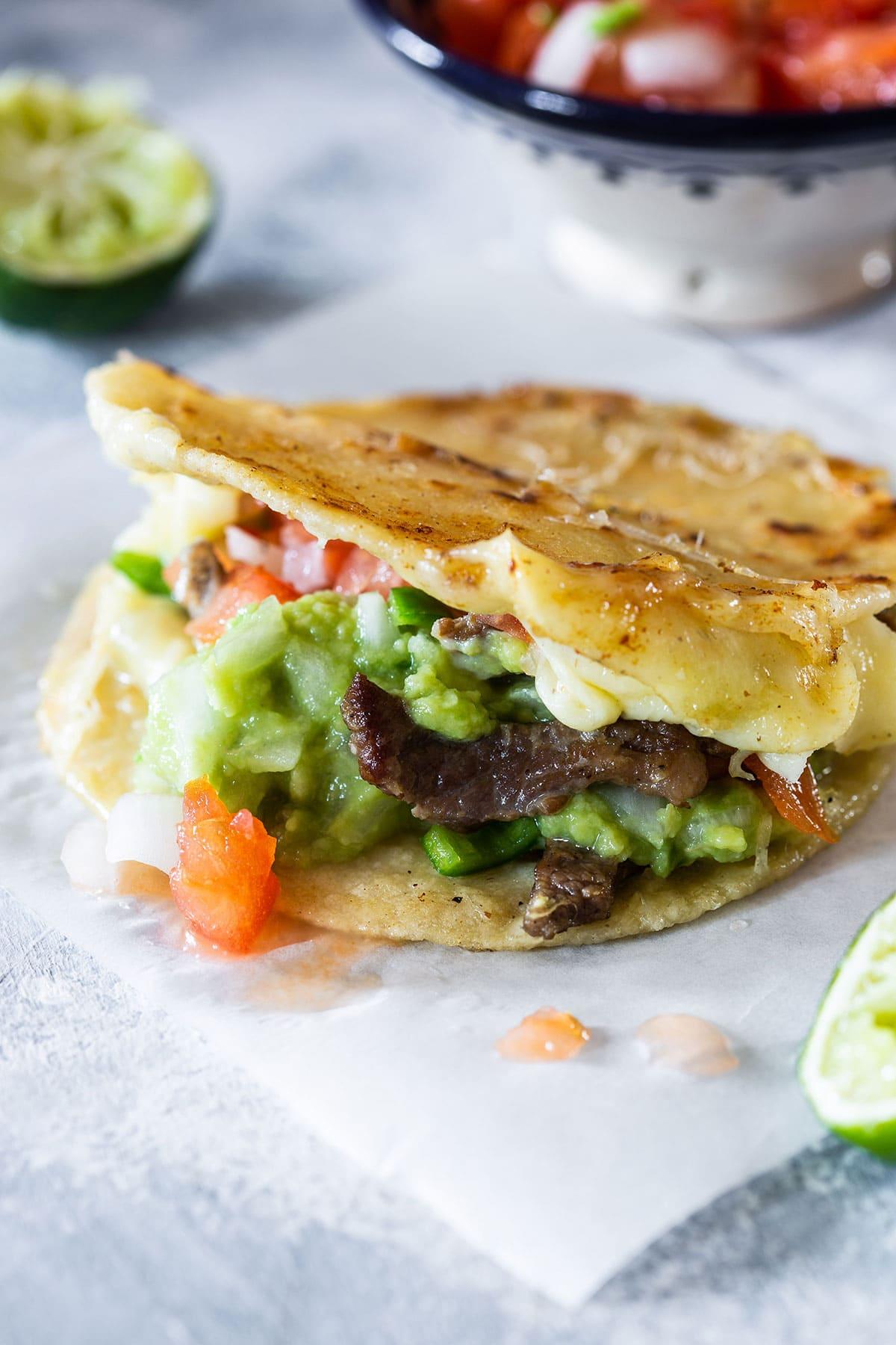 A mulita stuffed with carne asada, cheese, guacamole and pico de gallo salsa.