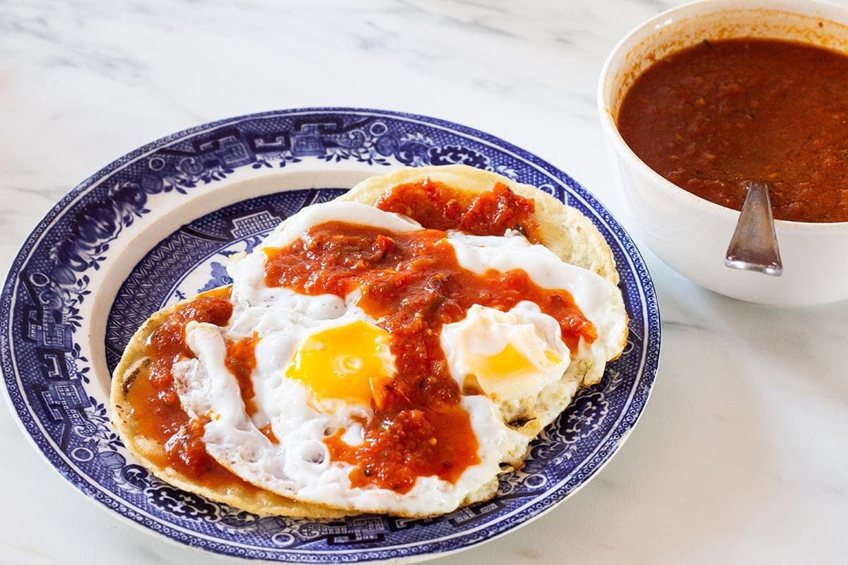Eggs on tortillas with salsa rancheros on top.