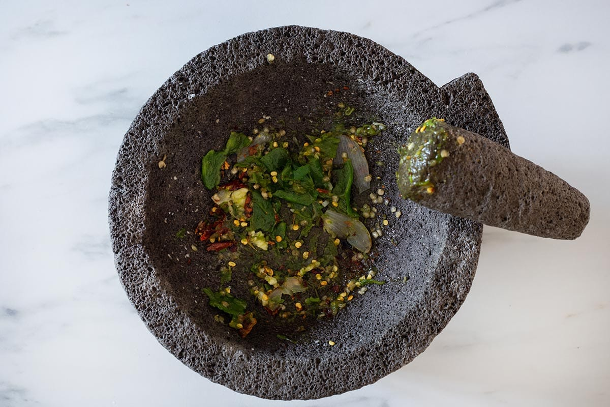 Mashing chilies and other ingredients on molcajete.