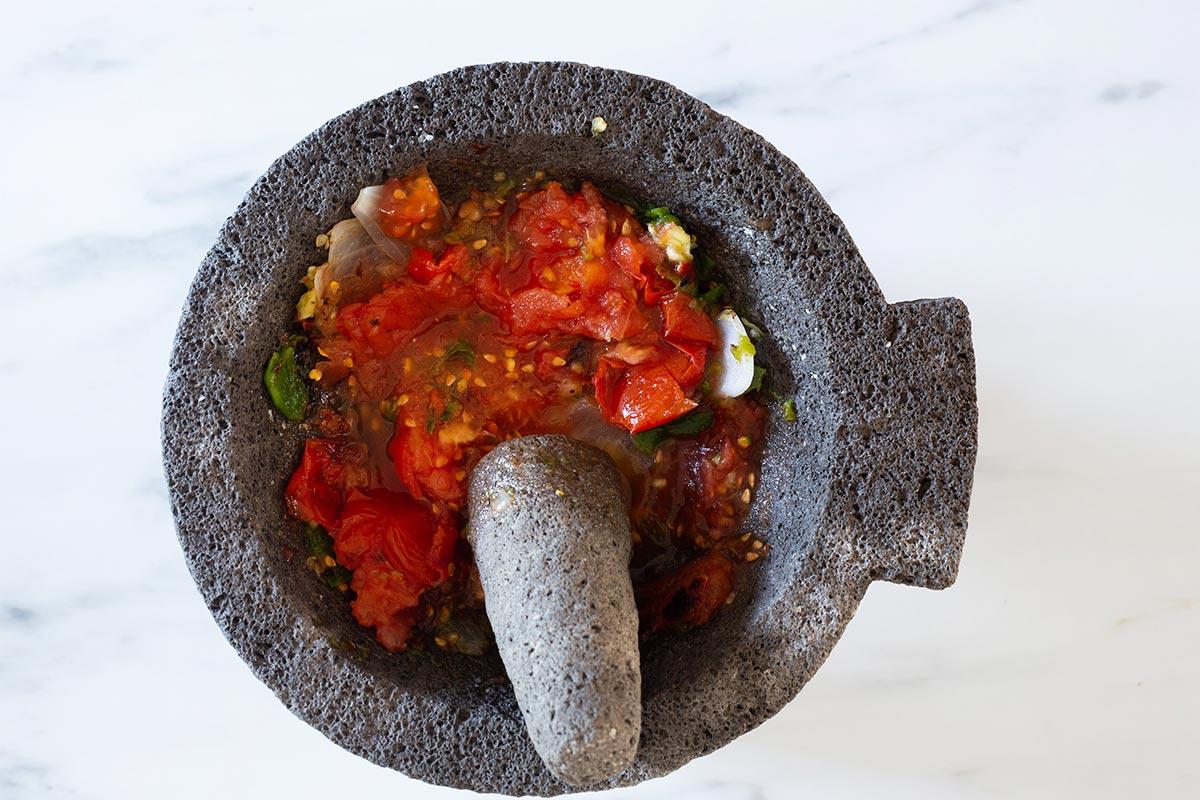 Mashing tomatoes on molcajete.