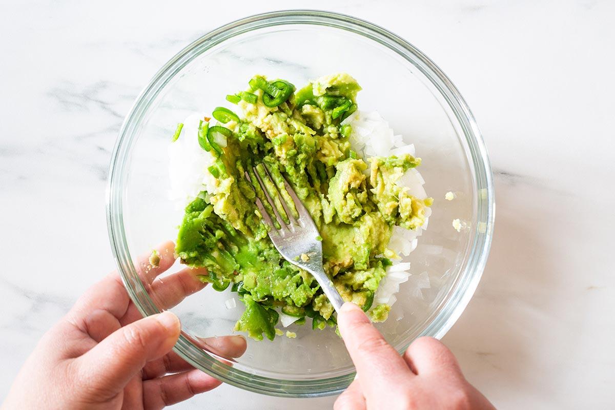 Smashing avocados into a bowl.