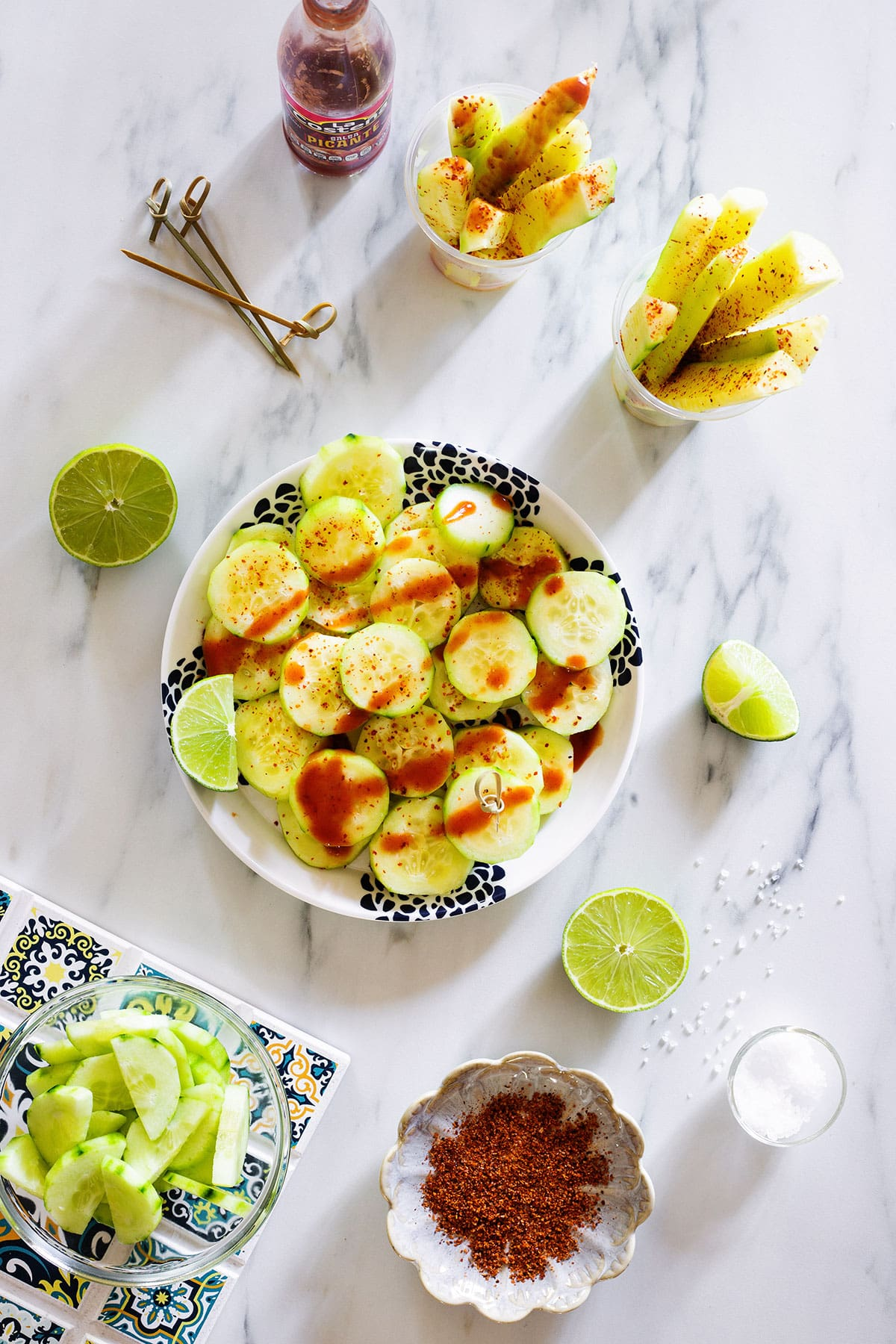 A plate and some cups with Mexican cucumber snack.