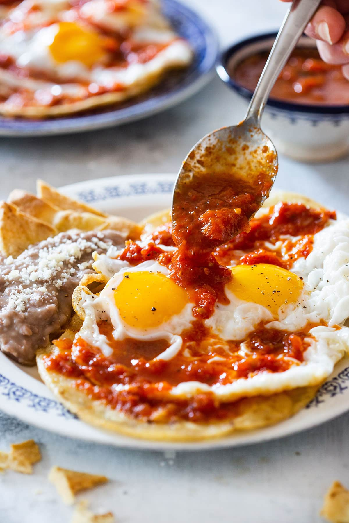 Huevos rancheros being drizzled with salsa.