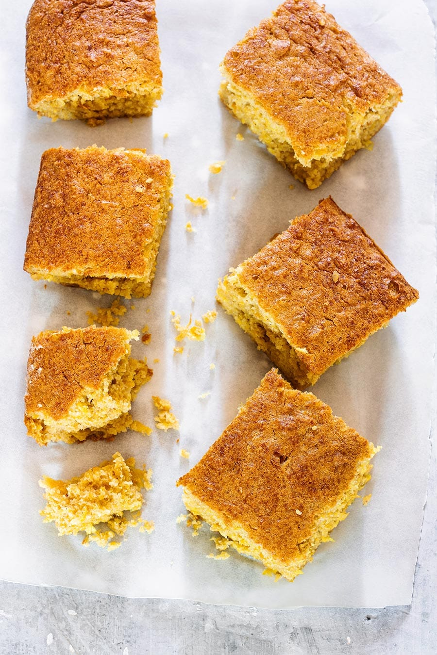 Pastel de elote (aka pan de elote) cut into squares and placed on parchment paper (seen from above).