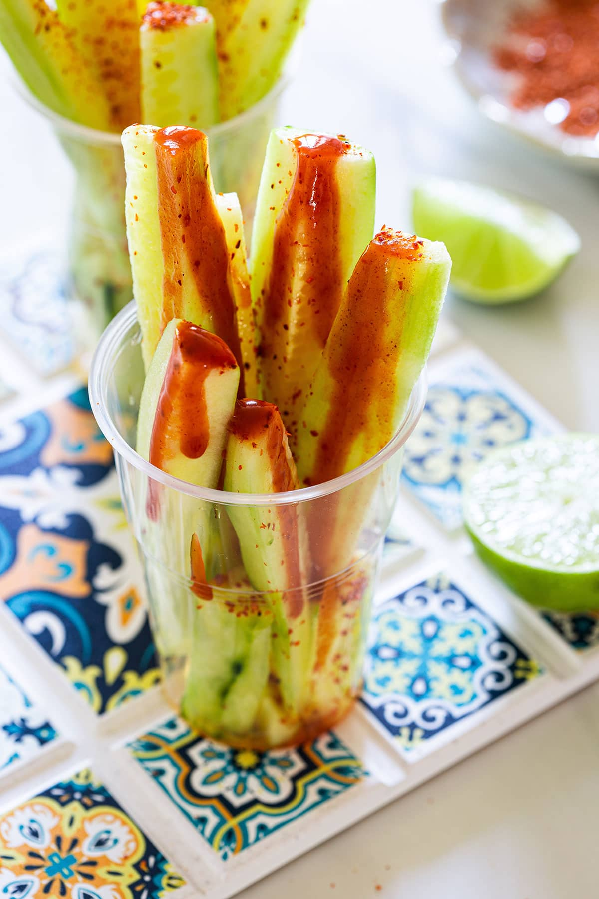 A close up of spears of cucumbers dressed with hot salsa, lime juice and chili powder.