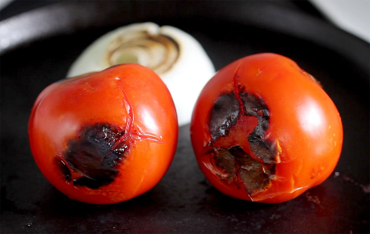 Roasted tomatoes and onions on a comal.