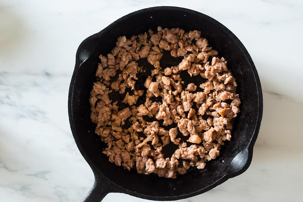 Lightly browned sausage on a cast iron skillet.