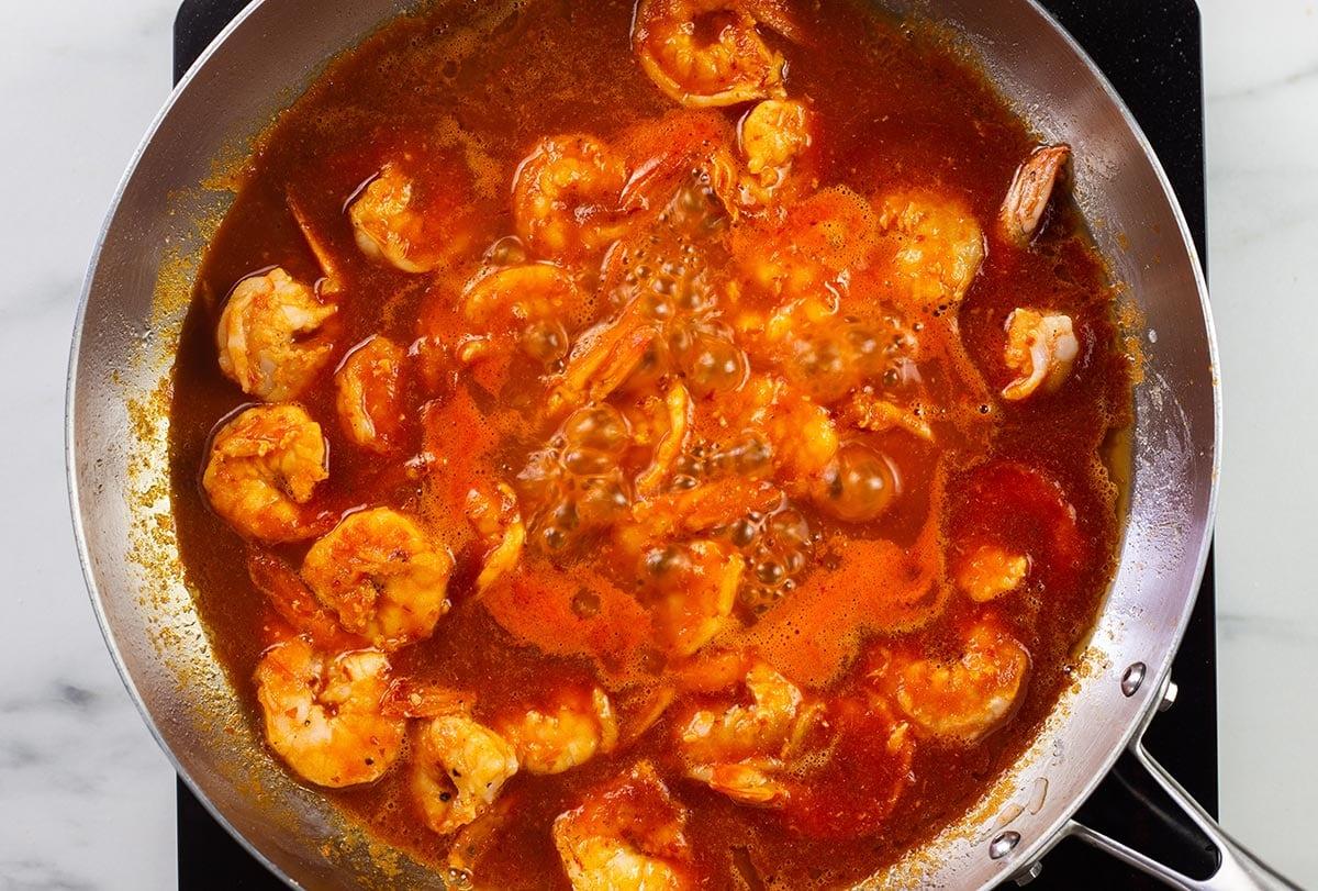 Simmering shrimps in diabla sauce.