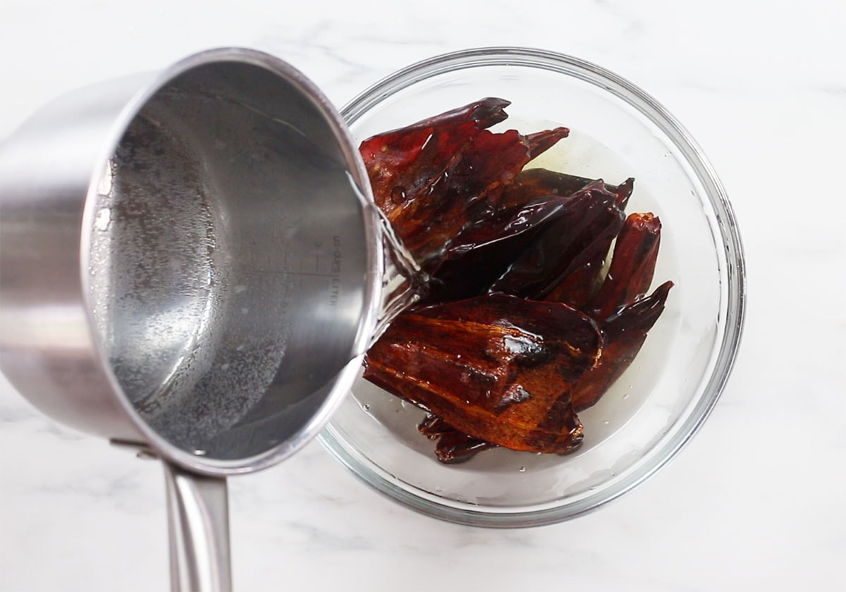 Adding hot water over chilies on a bowl.