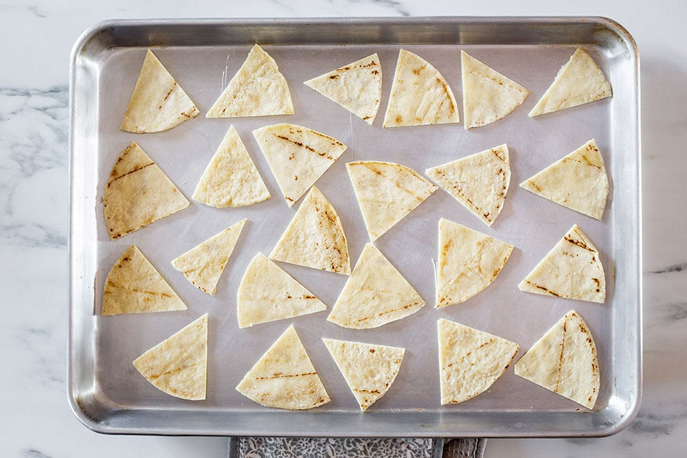 Tortilla triangles arranged on a baking tray.