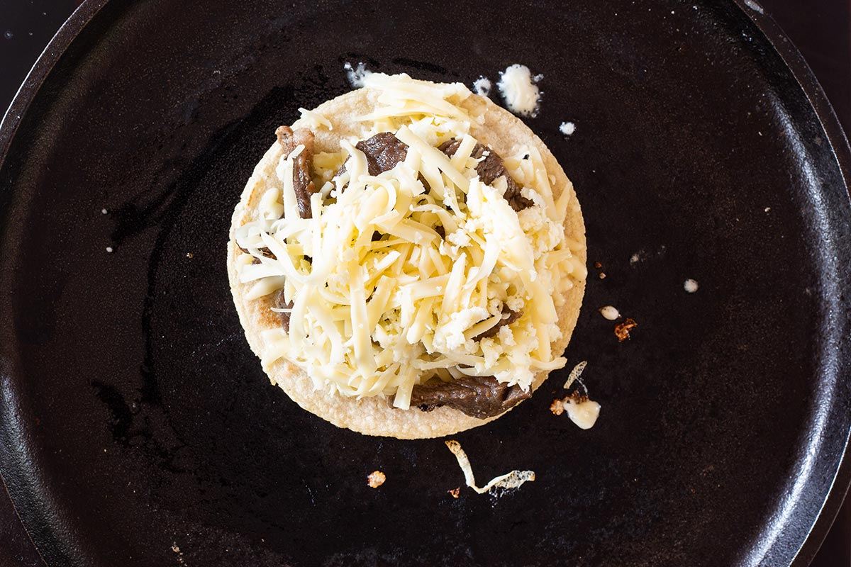 Tortilla on skillet with cheese and beef steak on top.