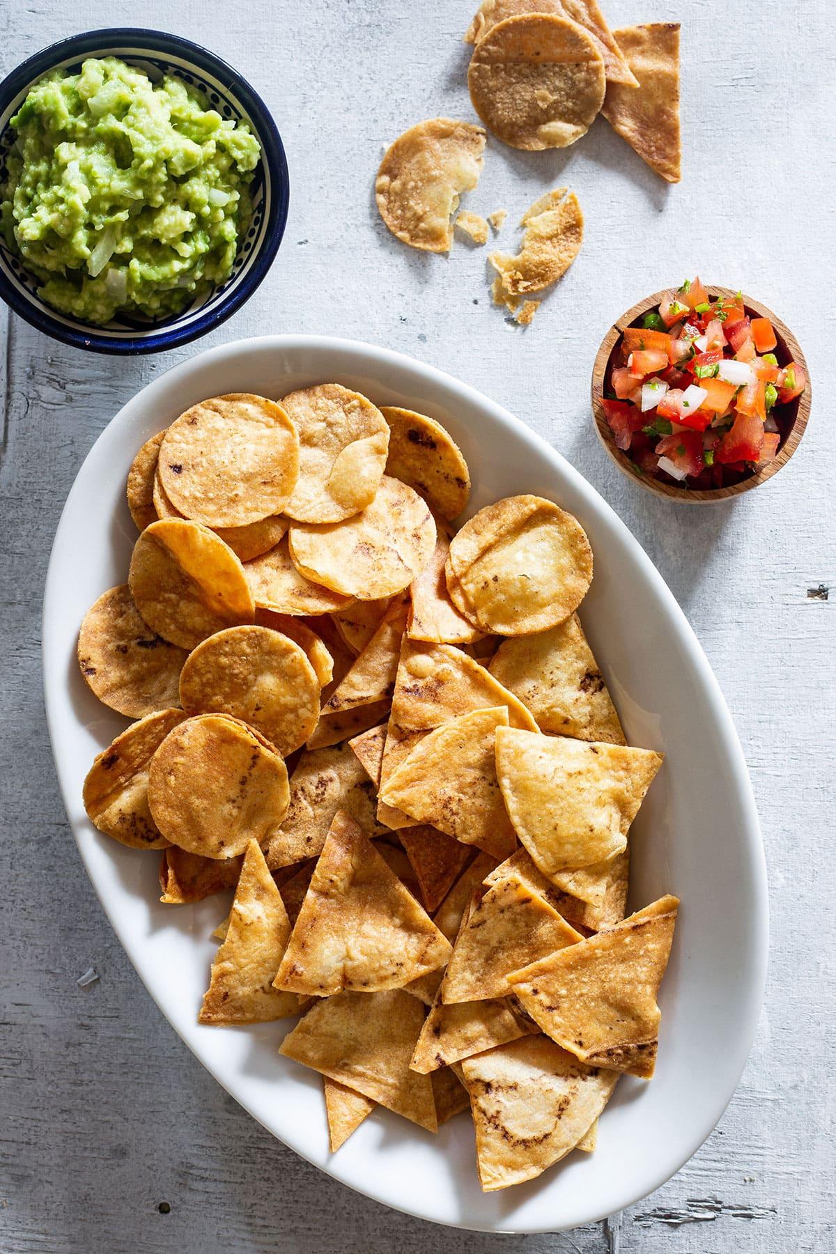 Totopos served with guacamole and pico de gallo salsa.