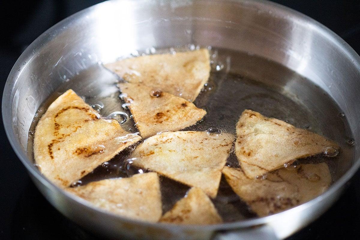 Medium fried totopos on a pan.