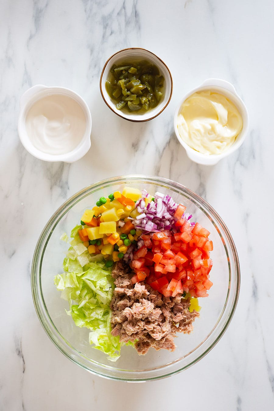 Vegetables and tuna on a bowl, and dressing ingredients on small bowls alongside.