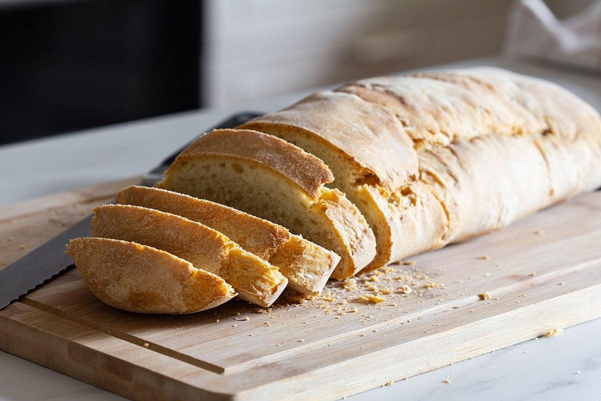 Crusty bread sliced on a cutting board.