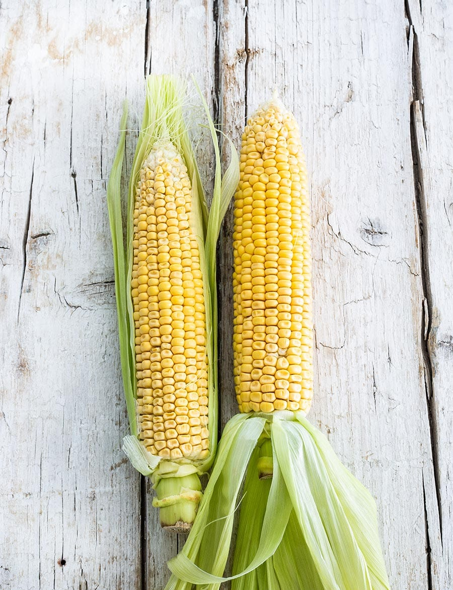 Corn on the cob on a wooden white surface.