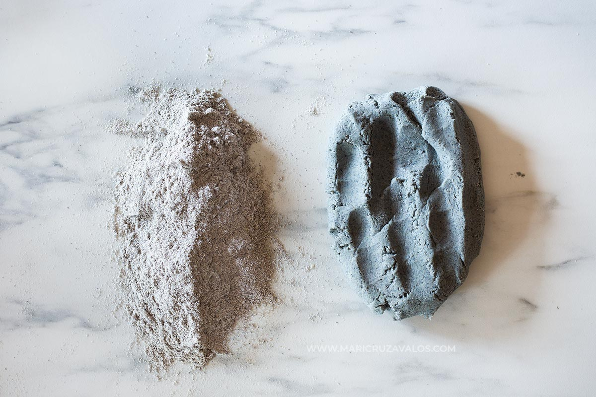 Blue corn flour and masa prepared on a marble countertop.