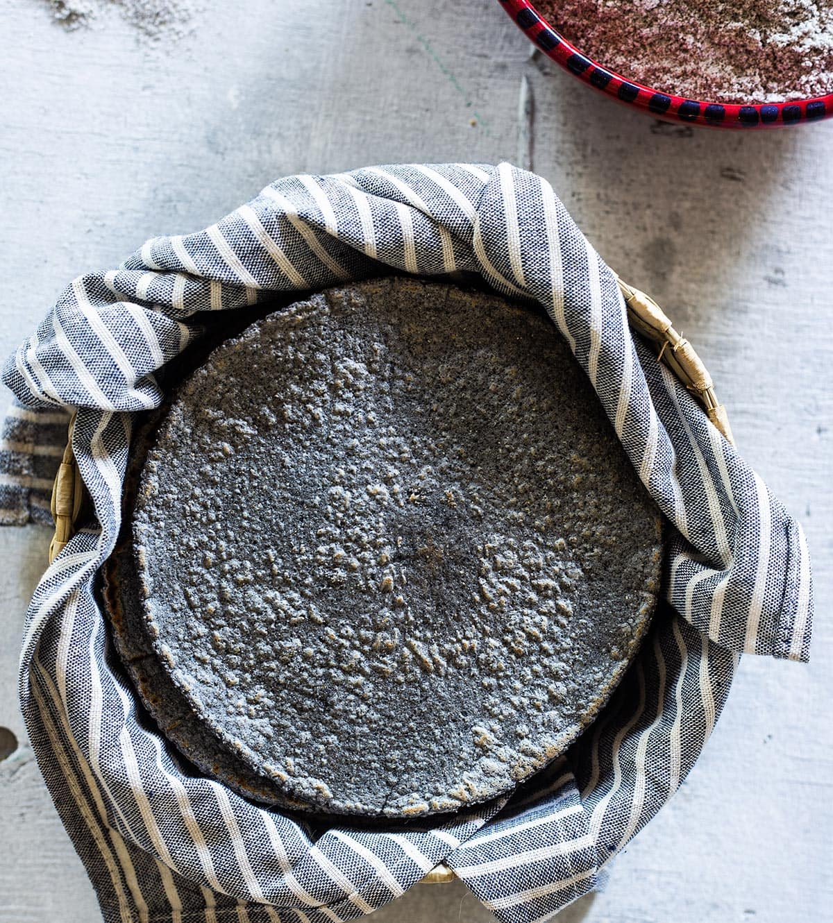 Blue corn tortillas wrapped in a kitchen towel and placed inside a small basket.