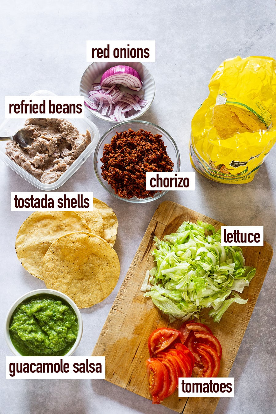 Tostadas toppings displayed on a concrete surface.