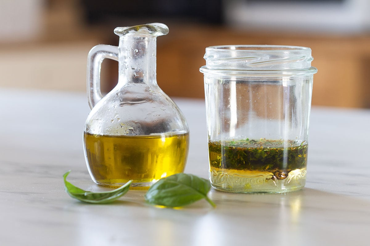 Olive oil in a bottle and ingredients for dressing in a jar.