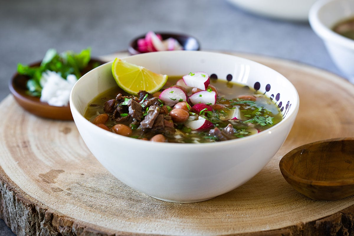 Carne en su jugo served with chopped onions, cilantro and radishes, and a lime wedge.