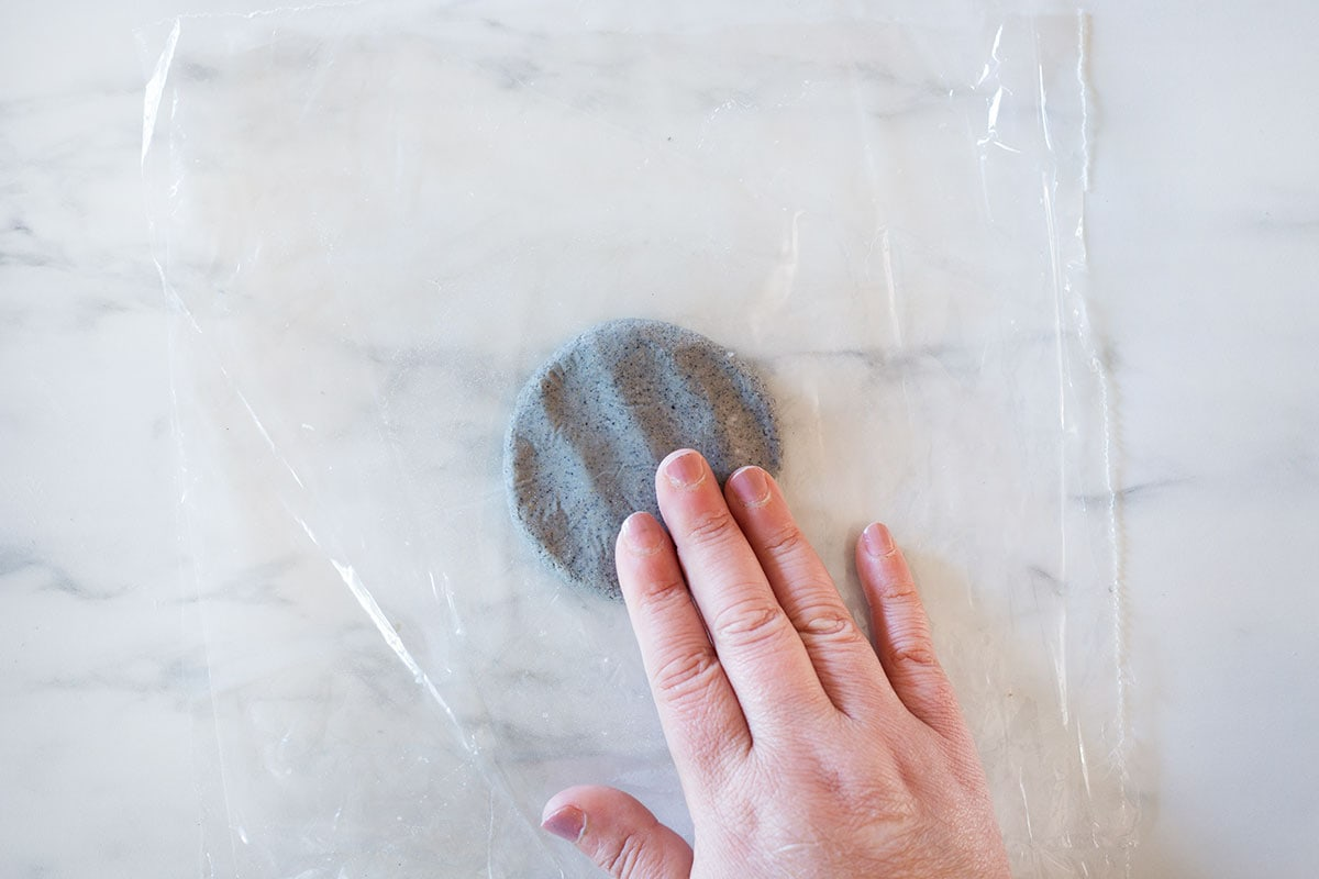 Making a patty with masa between two sheets of plastic.