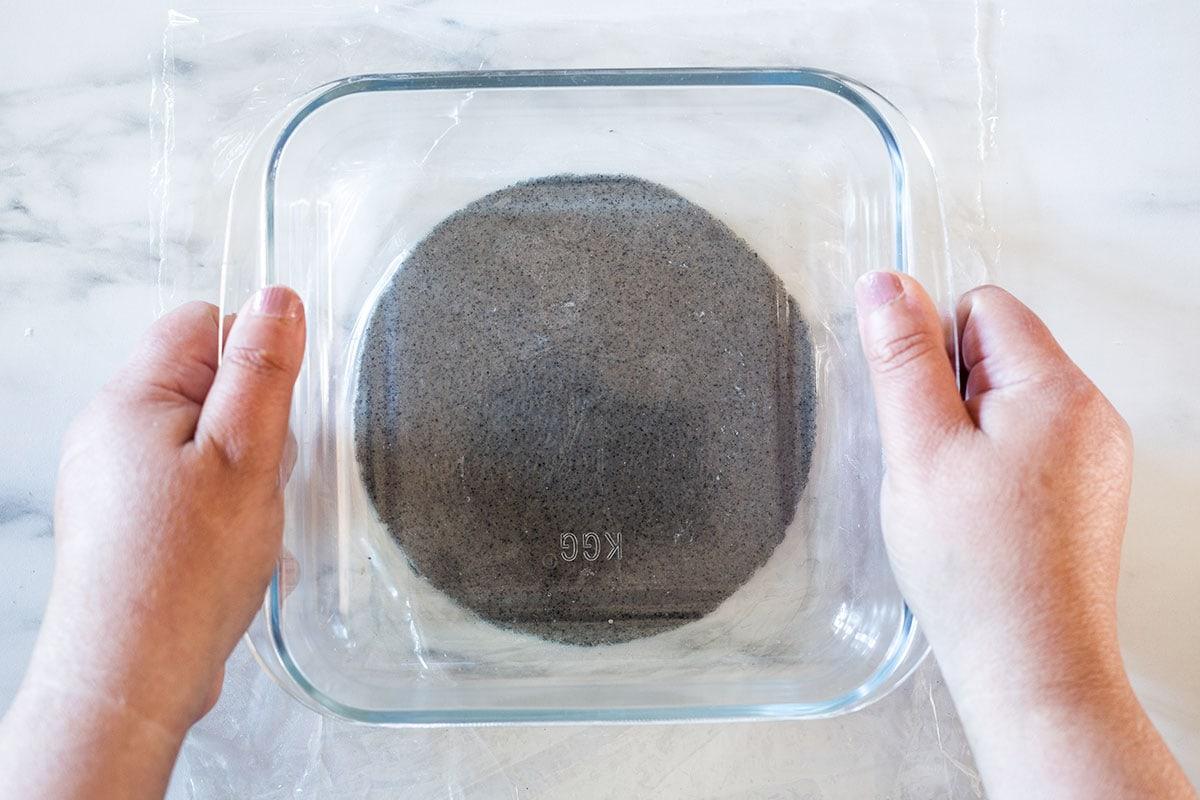 Pressing a heavy dish onto the masa patti to form a tortilla.