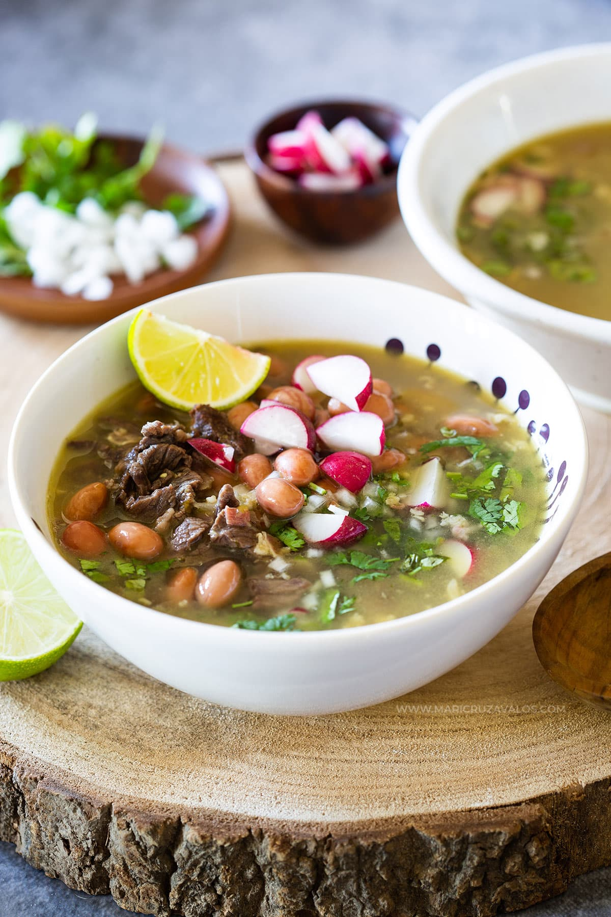 Mexican carne en su jugo served with various toppings.