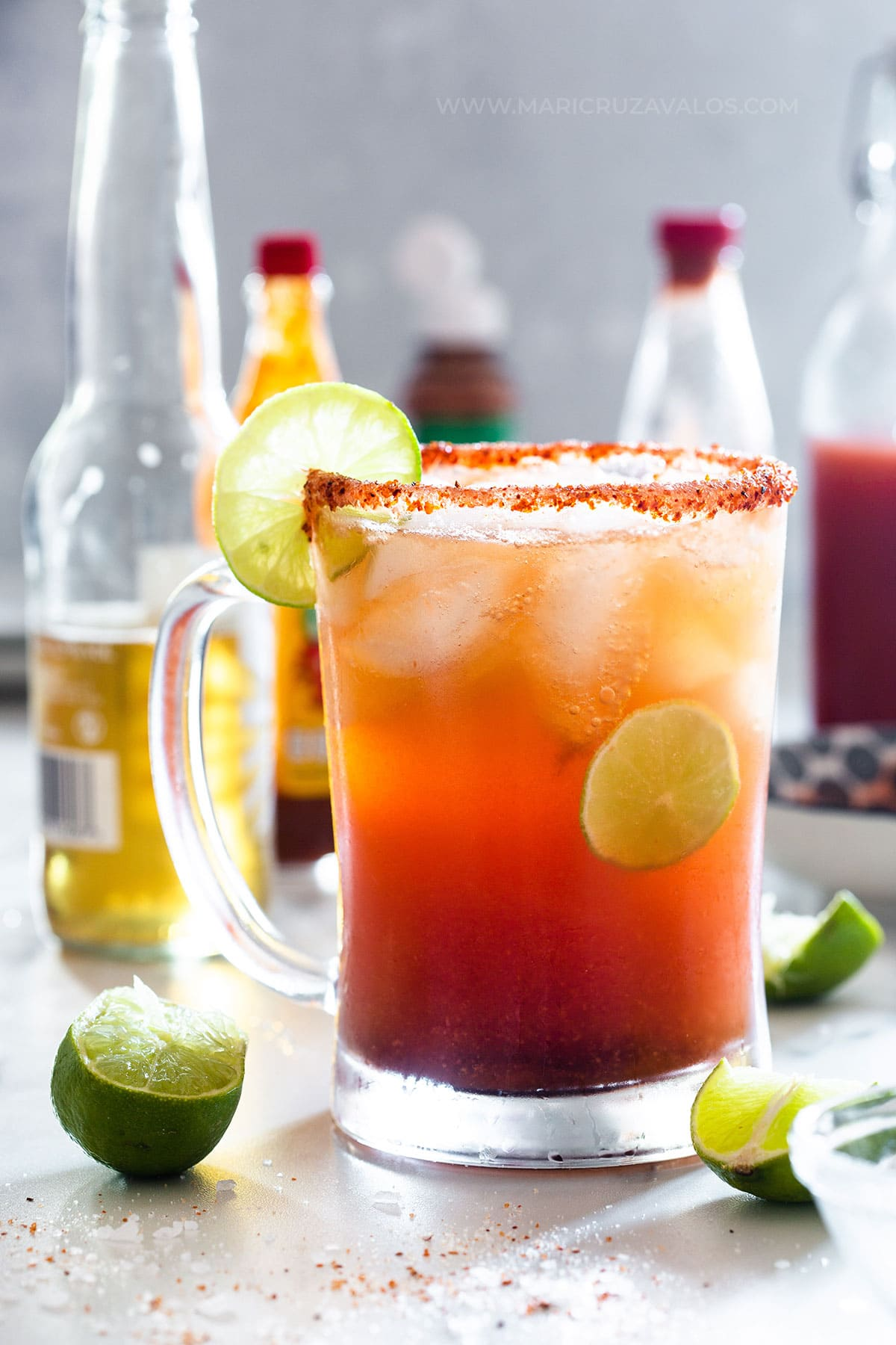 Michelada served on a cold glass garnished with lime slices.