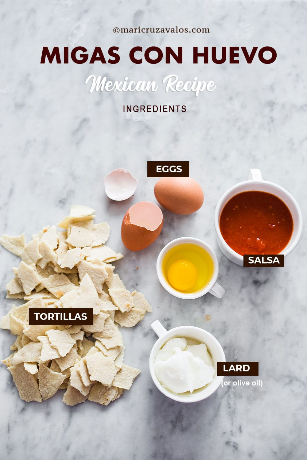 Migas con huevo ingredients labeled and displayed on a marble surface.
