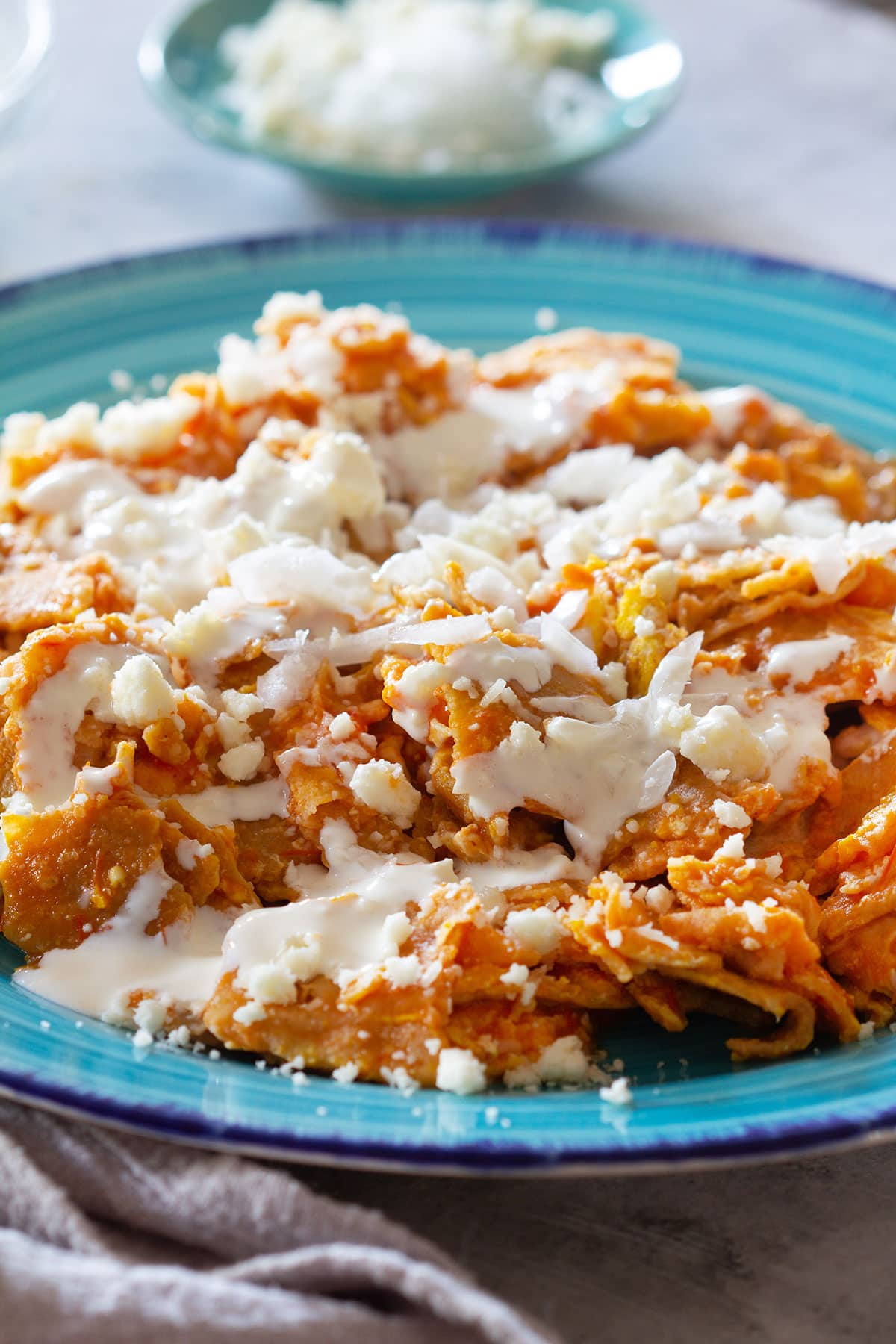 Migas breakfast topped with onions. fresh cheese and cream.