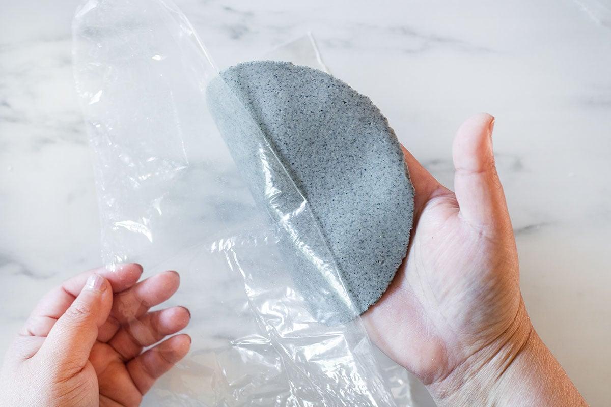 Peeling tortilla from plastic sheets.