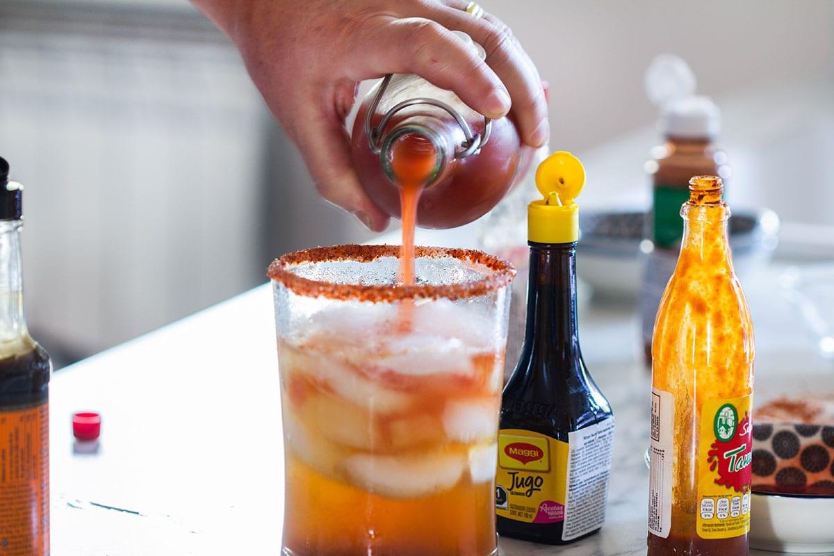 Pouring Clamato juice.