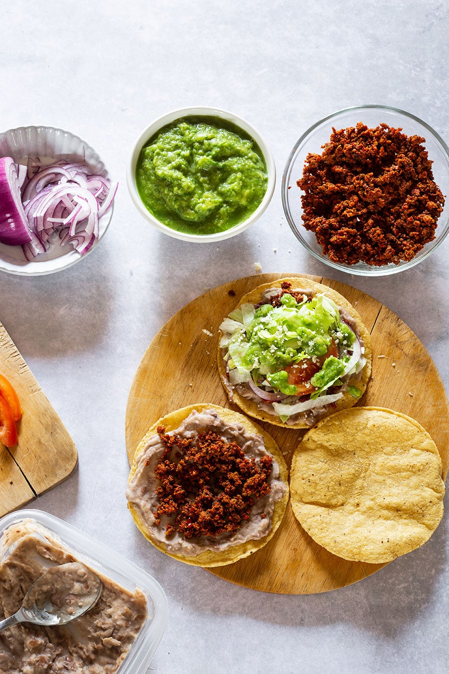 3 tostadas on a cutting board prepared with some ingredients.