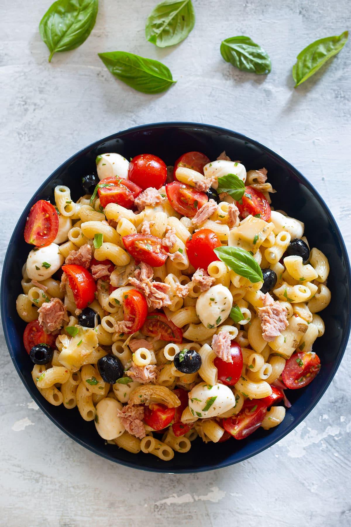 Tuna pasta salad on a dark blue bowl.