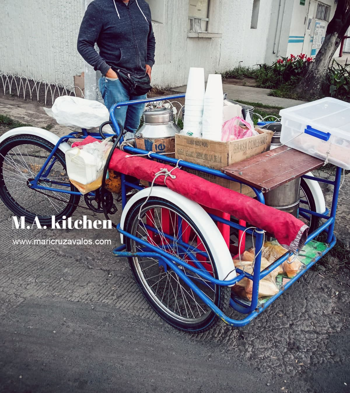 A man selling atole and tamales in a cart.
