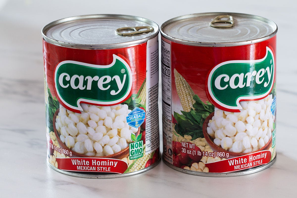 Two cans of precooked hominy from brand Carey.