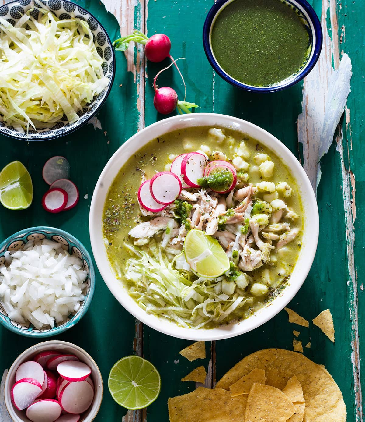 Chicken green pozole verde with various toppings.