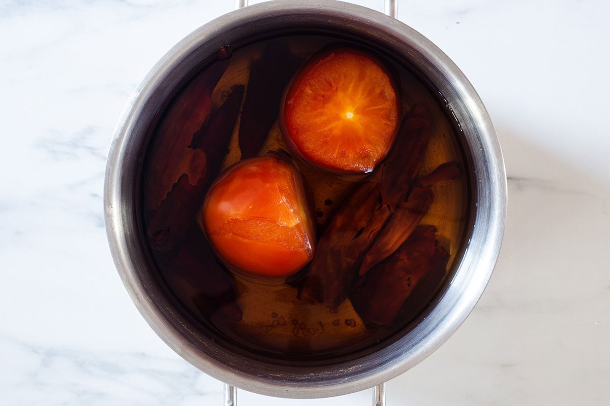 Boiled tomatoes and chilies on a pot.