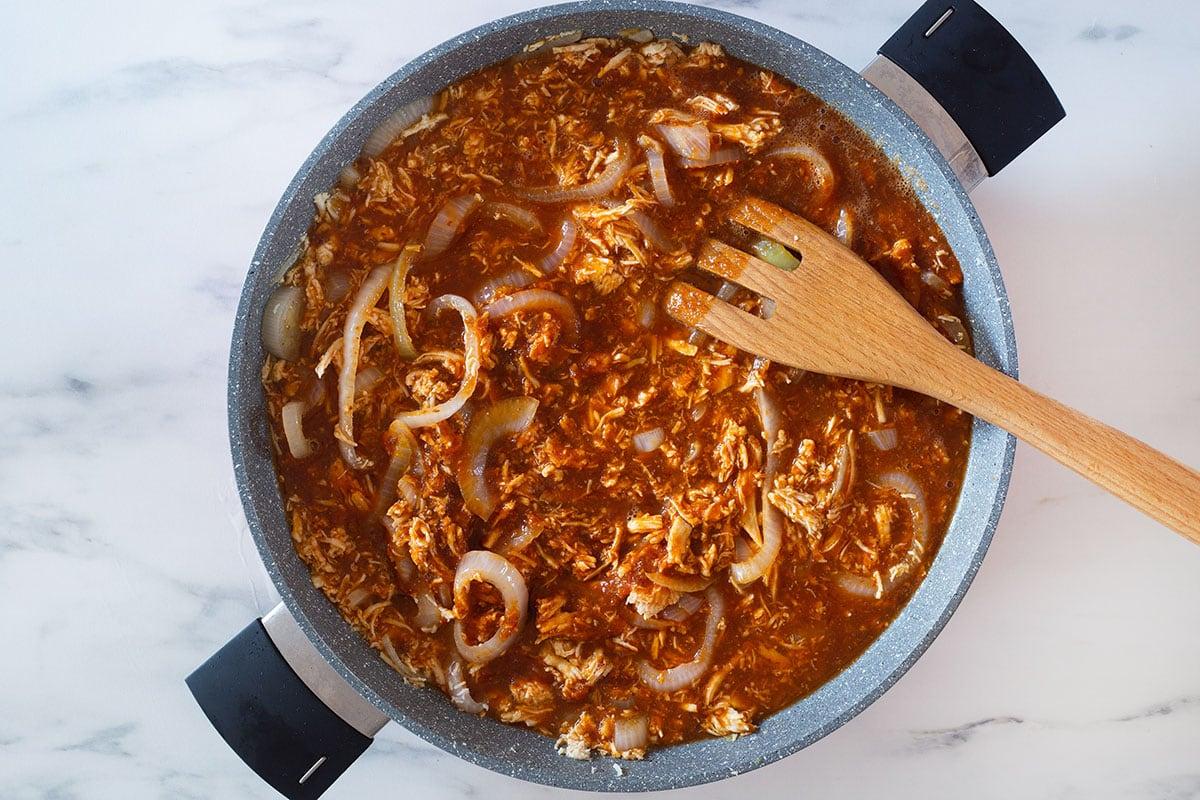 Cooking tinga de pollo in a medium pan.