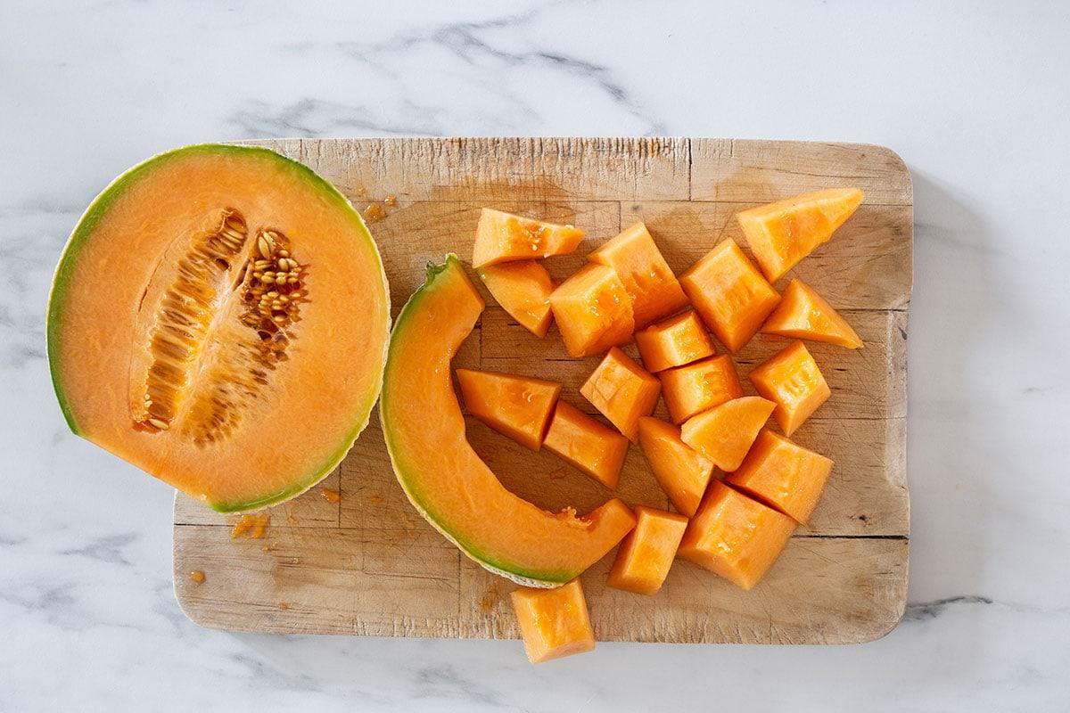 Cut melon on a cutting board.