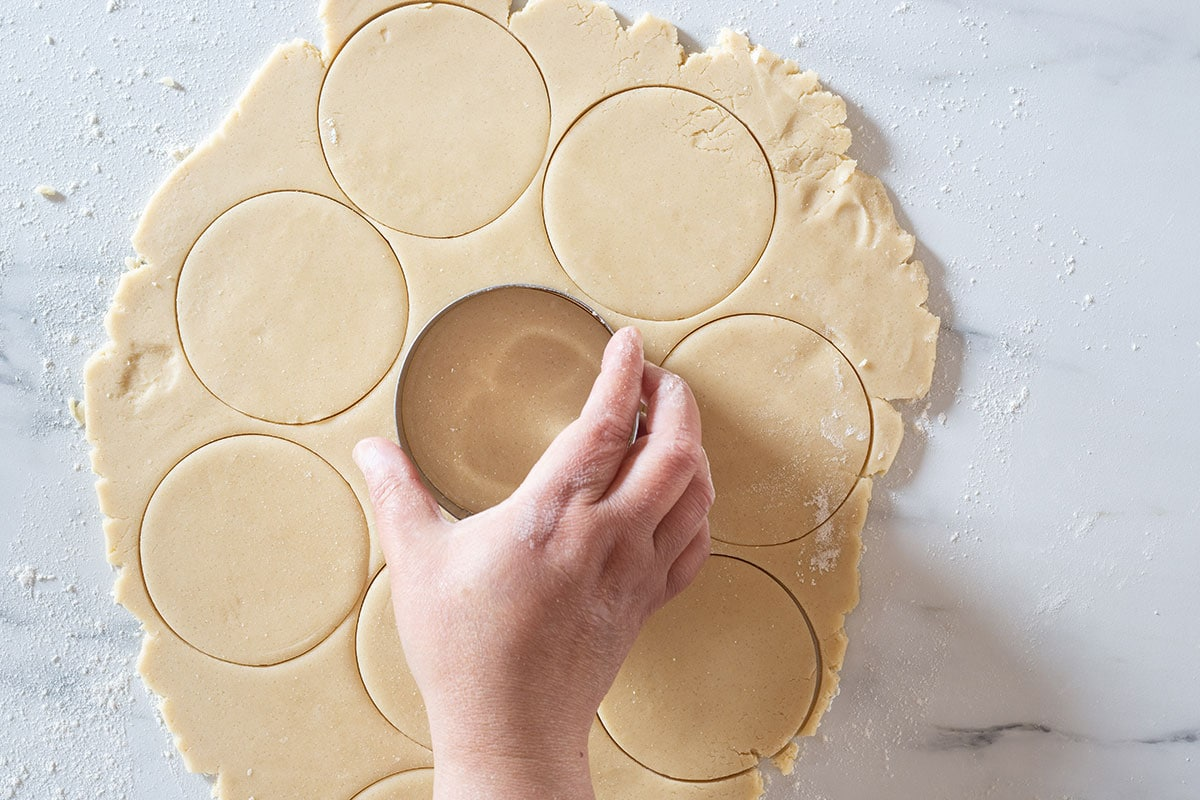 Cutting the dough with a round cookie cutter.